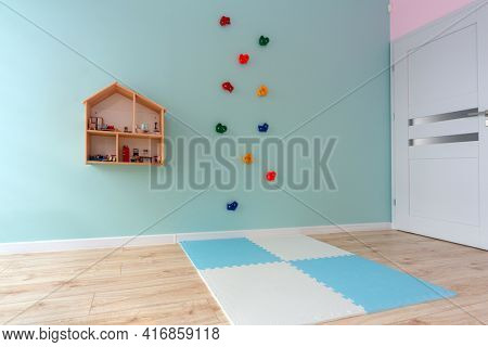 Turquoise children playroom with climbing wall and toys