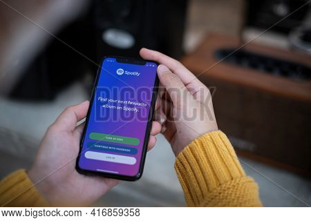 Chiang Mai, Thailand Apr 14 2021 : Smartphone And Using Spotify Application On The Screen And Sync T