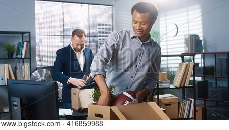 Portrait Of Mixed-races Male Professionals Entering Room Moving Into New Office Holding Boxes And Un