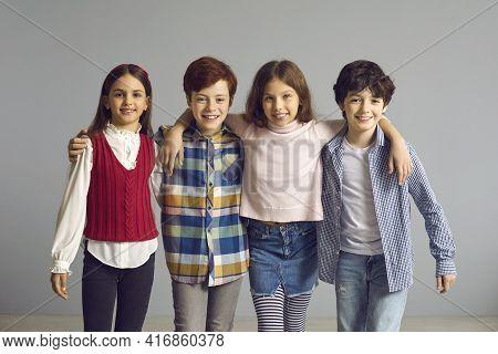 Studio Portrait Of Happy Little Kids Standing Together, Huddling And Smiling At Camera