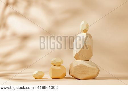 Composition of geometric wooden balancing stones with leaves shadow. Concept of balance, eco frendly. Pastel background with copy space.