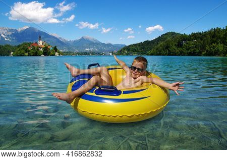Little boy on inflatable ring in the lake . Child on rubber yellow circle resting in nature. Bled. Slovenia, Europe.