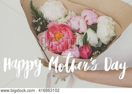 Happy Mother's Day. Happy Mother's Day Text And Hand Holding Beautiful Peonies Bouquet In Paper On B