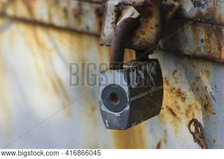 Rusty Old Padlock On Metal Gate Closeup. Dirty Lock On Closed Grey Painted Front Door. Protection, S