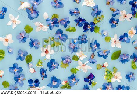 Floral Pattern From Blue, White Flowers, Green Leaves On A Blue Background. Flat Lay, Top View. Flor