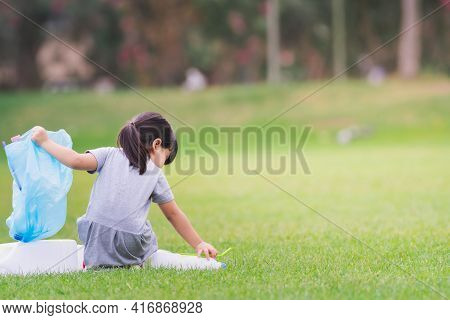 Child Collect Garbage On Lawn. Asian Girl Puts Plastic Bottle In Blue Bag. Kid Take Care Of Environm