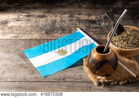 Yerba Mate Tea And Argentina Flag On Wooden Table. Traditional Argentinian Beverage. Copy Space