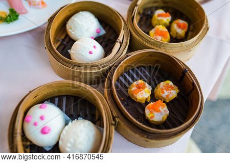 Chinese Bun With Minced Pork And Dim Sum, Traditional Chinese Dumplings, In Bamboo Steamer Basket