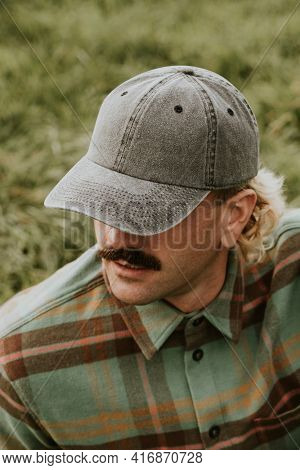 Man with mustache wearing a cap and green flannel shirt