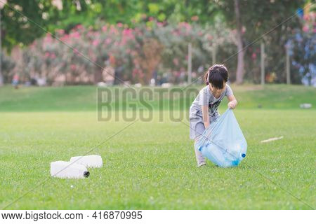 Child Takes Care Of Environment. Cute Asian Girl Keeps Plastic Bottle Bags In Blue Plastic Bag. Chil