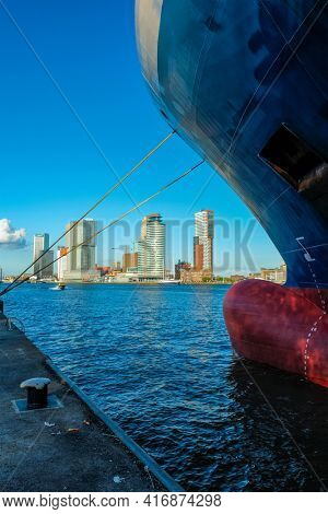 View of Rotterdam skyscrapers skyline from under cargo vessel moored to the quay of Nieuwe Maas river