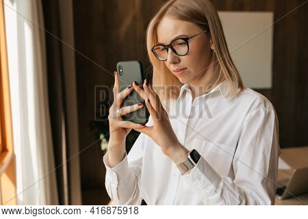 Happy Successful Young Girl Takes A Photo Of The City From The Window Of Her Office. Photo On A Smar