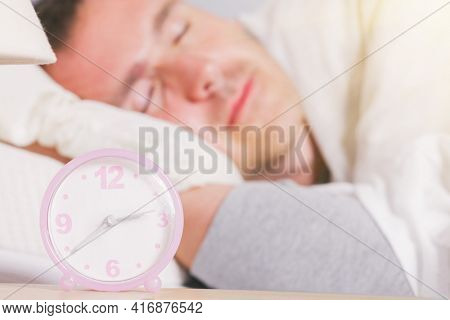 Man is sleeping at home. The alarm clock visible in the foreground