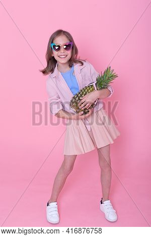 Little Smiling Girl Lying On Floor And Playing With Pineapple And Toy, Laptop In Background. Concept