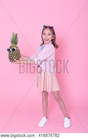 Studio Shot Of Lovely Long Haired Foxy Girl Has Charming Look, Holds Pineapple On Head, Concentrated