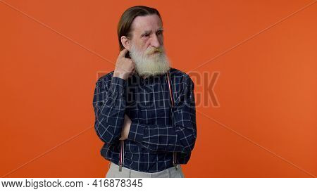 Thoughtful Clever Senior Old Bearded Man Rubbing His Chin And Looking Aside With Pensive Expression,