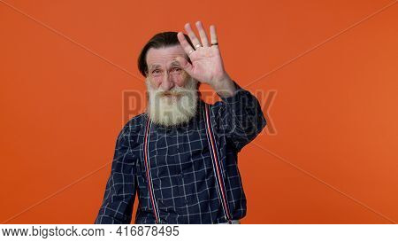 Happy Friendly Elderly Bearded Man Waves Hand Palm In Hello Gesture Welcomes Someone With Hospitable