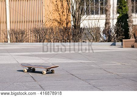 Old Wooden Skateboard On A Skating Rink In An Open-air Park. Equipment For The Youth Sport Of Skateb