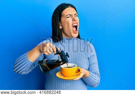 Beautiful brunette woman holding french coffee maker pouring coffee on cup angry and mad screaming frustrated and furious, shouting with anger. rage and aggressive concept.