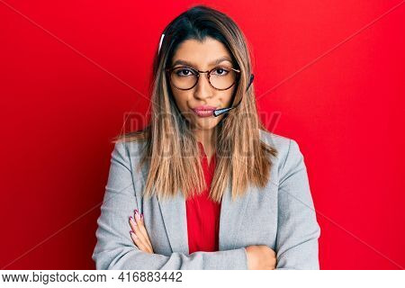 Beautiful brunette woman working at the office wearing operator headset skeptic and nervous, disapproving expression on face with crossed arms. negative person.