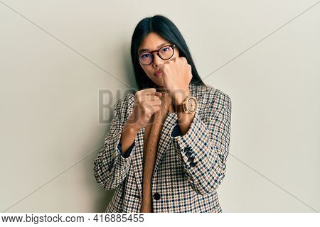 Young chinese woman wearing business style and glasses ready to fight with fist defense gesture, angry and upset face, afraid of problem