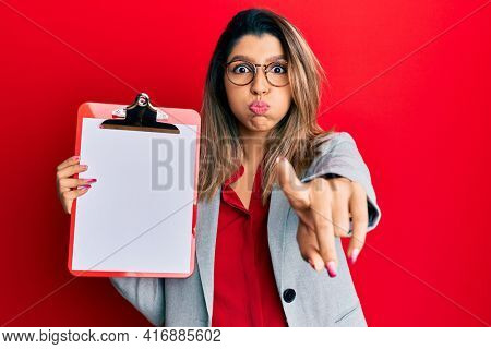 Beautiful brunette woman holding clipboard with blank space puffing cheeks with funny face. mouth inflated with air, catching air.