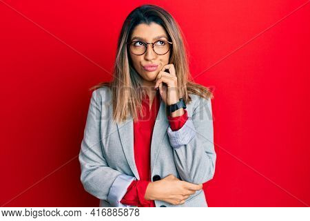 Beautiful brunette woman wearing business shirt and glasses thinking concentrated about doubt with finger on chin and looking up wondering