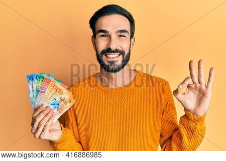 Young hispanic man holding swiss franc banknotes doing ok sign with fingers, smiling friendly gesturing excellent symbol