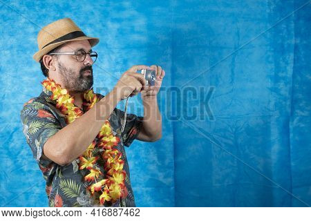 Person Dressed As A Tourist With Printed Shirt And Photo Camera In Hand