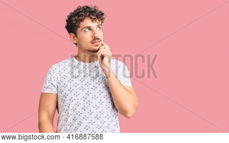 Young handsome man with curly hair wearing casual clothes serious face thinking about question with hand on chin, thoughtful about confusing idea