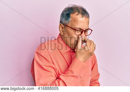 Middle age indian man wearing casual clothes and glasses smelling something stinky and disgusting, intolerable smell, holding breath with fingers on nose. bad smell