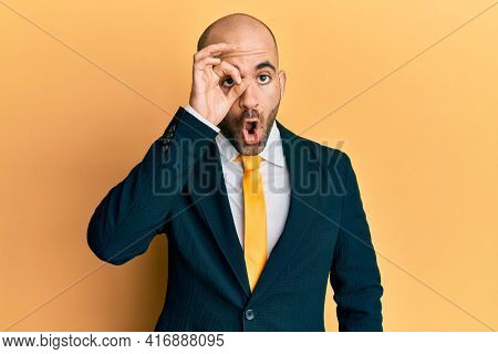 Young hispanic man wearing business suit and tie doing ok gesture shocked with surprised face, eye looking through fingers. unbelieving expression.
