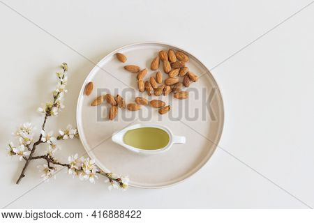 Blooming Almond Twigs Macerating In Almond Oil, To Prepare A Skin Tonic, Earthenware Plate And White