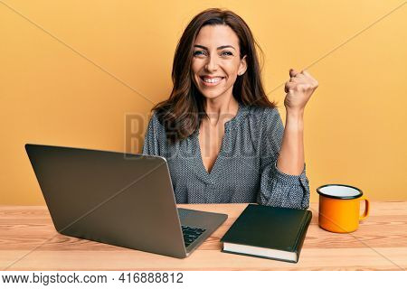 Young brunette woman working using computer laptop screaming proud, celebrating victory and success very excited with raised arm