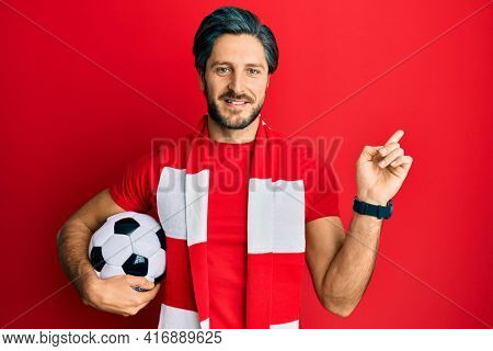 Young hispanic man football hooligan holding ball smiling happy pointing with hand and finger to the side