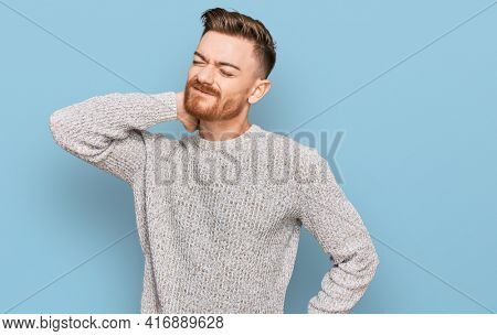 Young redhead man wearing casual winter sweater suffering of neck ache injury, touching neck with hand, muscular pain