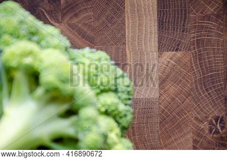 Selective Focus Wooden Surface And Broccoli On Blurred Foreground. Fresh Head Of Broccoli Lies On Wo