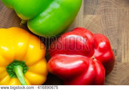 Selective Focus Yellow, Green And Red Bell Peppers Background With Copy Space. Ripe Red Peppers In T