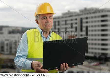 Elderly Builder Man Wearing Yellow Protective Hardhat And Fluorescent Vest With Focused Expression L