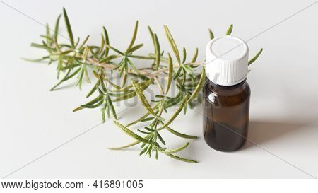 A Bottle Of Essential Oil With Fresh Rosemary Twigs In The White Background. Relaw With A Spa Concep