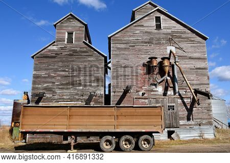 A Grain Trailer Is Parked In Front Of Several Very Old Rickety Wooden  Grain Elevators