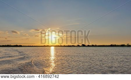 Sunset Over The Zambezi River. The Sun Colors The Sky And Clouds In Golden Hues. There Are Ripples A