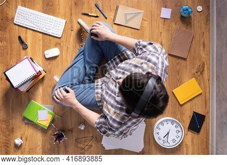 Man relaxing on floor thinking idea solitions. Man student studying online lesson listening music. Creative inspiration study concept