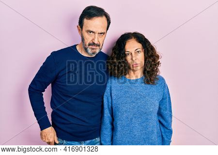 Middle age couple of hispanic woman and man hugging and standing together skeptic and nervous, frowning upset because of problem. negative person.