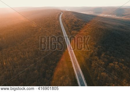 Aerial Drone Overhead Of A Straight Road Through Leafless Forest Valley At Sunset. Highway Go Throug