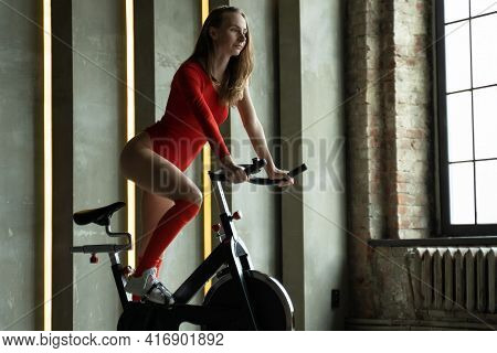 Fitness Woman In Red Bodysuit Exercising On Stationary Cycling Machine In Gym