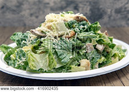 Caesar Salad Piled High With Cheese, Lettuce, And Dressing To Fill Any Appetite.