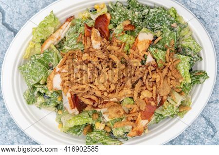 Overhead View Of Bbq Chicken Salad Piled High With Romaine, Chicken Breast, Lettuce, And Dressing To