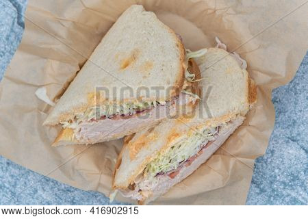 Overhead View Of Roasted Turkey Sandwich Stacked Inside Sour Dough Bread Loaded With Meat, Fillings