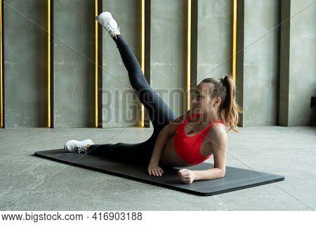 Smiling Woman Raising Leg On Mat Over Gym Background